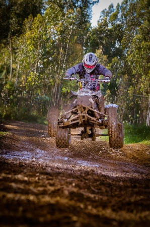 Quad rider jumping on a forest trail. photo