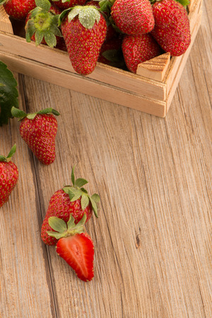 Strawberries over odl brown wooden table background photo