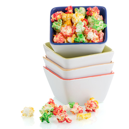 popcorn bowls: Pile of ceramic bowls of popcorn on white reflective background.