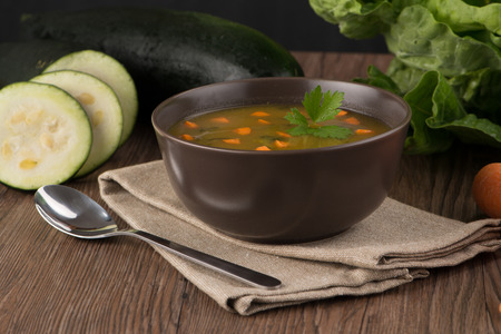 uncouth: Soup with vegetables on wooden table.