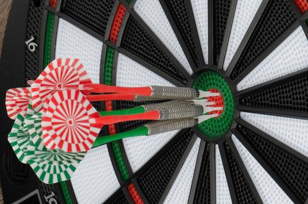 holed: Closeup of dart board with darts.