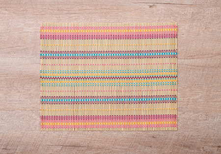 place mat: Bamboo place mat on wooden deck table.