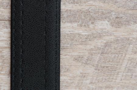 Leather belt over wooden background.