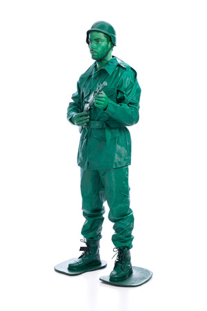 green military miniature: Man on a green toy soldier costume with riffle isolated on white background.