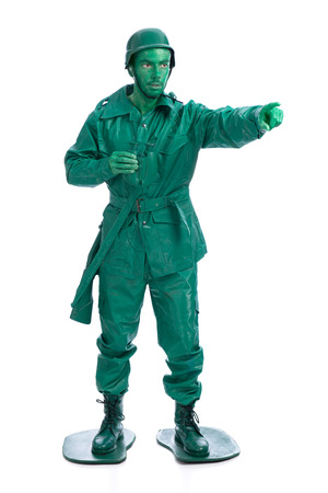 riffle: Man on a green toy soldier costume with riffle poiting with his forefinger  isolated on white background. Stock Photo
