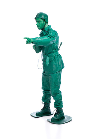 Man on a green toy soldier costume with riffle poiting with his forefinger  isolated on white background. photo