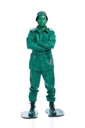 Man on a green toy soldier costume with arms crossed isolated on white background. photo