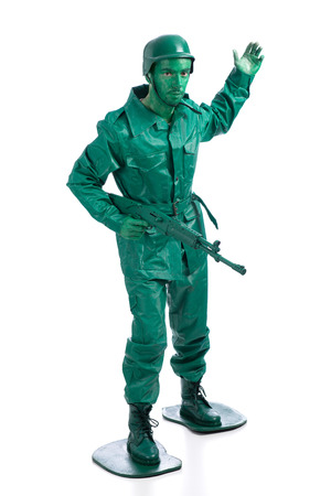 green plastic soldiers: Man on a green toy soldier costume with riffle waving to be followed  isolated on white background. Stock Photo