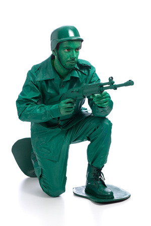 Man on a green toy soldier costume standing on one knee with riffle isolated on white background. photo