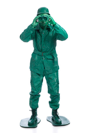 Man on a green toy soldier costume standing with binocolous isolated on white background. Stock Photo