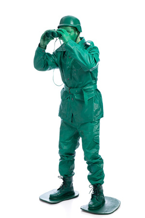green military miniature: Man on a green toy soldier costume standing with binocolous isolated on white background. Stock Photo