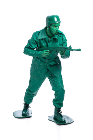 Man on a green toy soldier costume walking with riffle isolated on white background. photo
