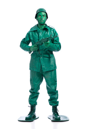 Man on a green toy soldier costume standing with riffle isolated on white background. photo