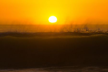 breaking down: Ocean wave breaking down at sunset time.