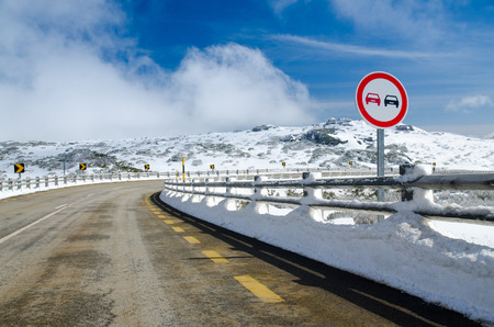 overtake: Overtake Forbidden Sign in a Snowy Road.