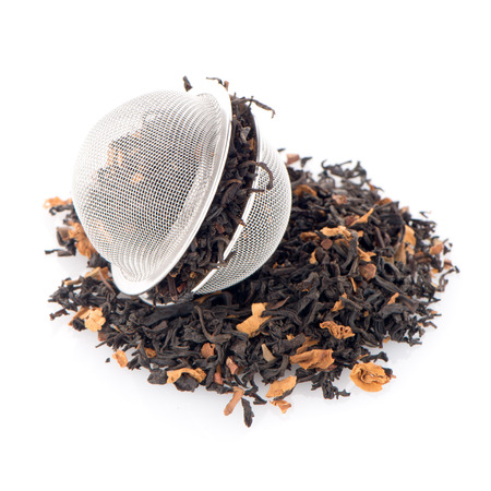 tea strainer: Aromatic black dry tea with petals and a tea strainer on white reflective background.
