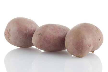 reflective background: Red potatoes on white reflective background. Stock Photo