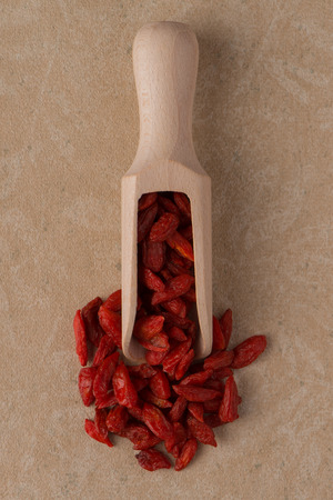 Top view of wooden scoop with dry red goji berries against brown vinyl background. photo