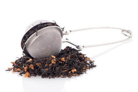 Aromatischer schwarzer trockener Tee mit Blütenblättern und einem Teesieb auf weißem reflektierenden Hintergrund.