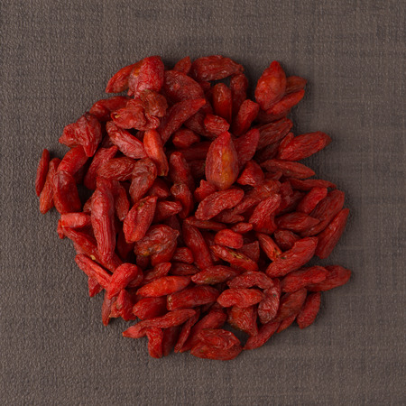 Top view of circle of dry red goji berries against brown vinyl background. photo