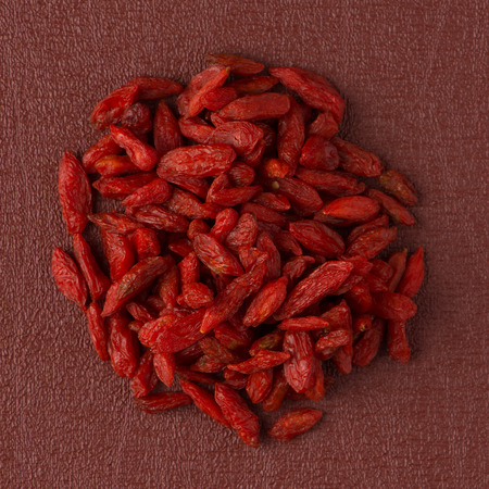 Top view of circle of dry red goji berries against red vinyl background. photo
