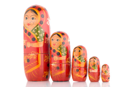 babushka: Five red Babushka on white reflective background.