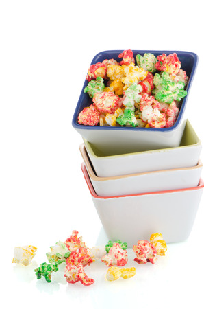 Pile of ceramic bowls of popcorn on white reflective background. photo