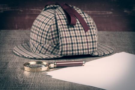 Deerstalker or Sherlock Hat and magnifying glass on Old Wooden table.