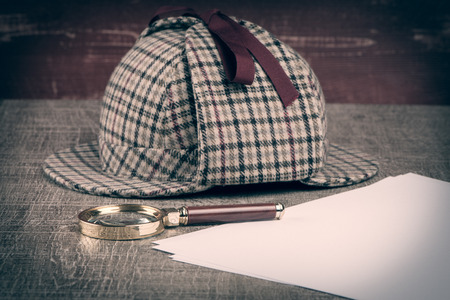 holmes: Deerstalker or Sherlock Hat and magnifying glass on Old Wooden table.