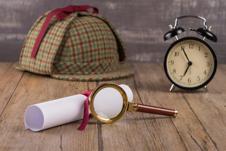sherlock holmes: Wrapped paper sheets and magnifying glass on Old Wooden table.