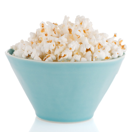 Popcorn in a blue bowl on a white background