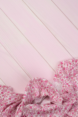 Pink towel over wooden kitchen table. View from above. photo
