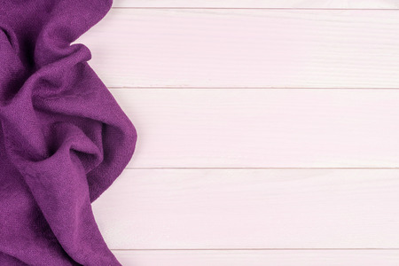 Purple towel over wooden kitchen table. View from above.