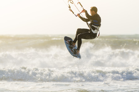 kiter: Kitesurfer jumping on a beautiful background of spray during the sunset. Stock Photo