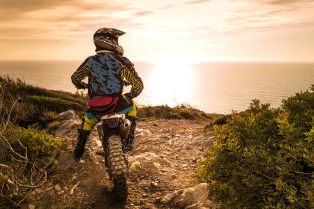 Enduro Racer sitzt auf seinem Motorrad den Sonnenuntergang beobachten.