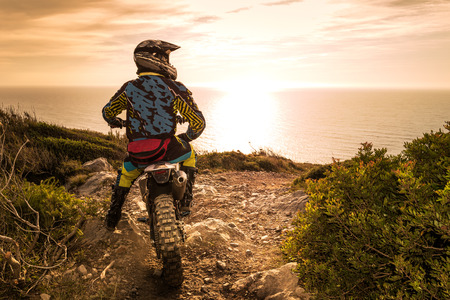 Enduro racer zittend op zijn motorfiets kijken naar de zonsondergang.