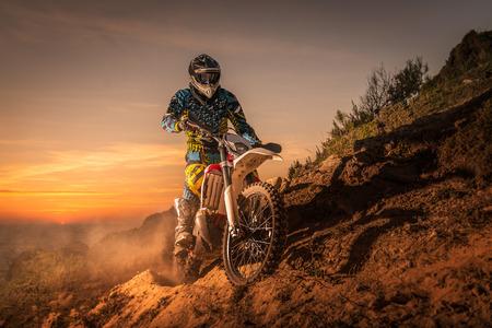 casco de moto: piloto de enduro subir una pendiente alta contra una hermosa puesta de sol en un paisaje marino.