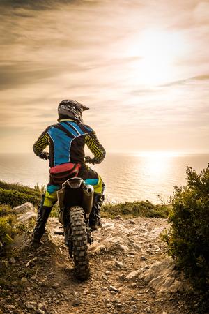 casco de moto: Piloto de Enduro que se sienta en su motocicleta ver el atardecer.