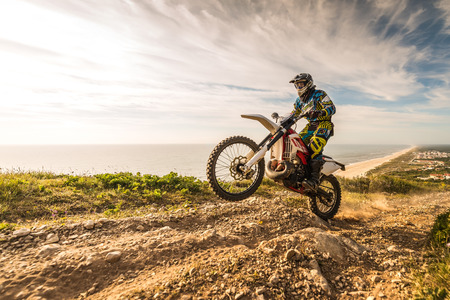 dirt road: Enduro rider climbing a steep slope against a beautiful sunset on a seascape Stock Photo