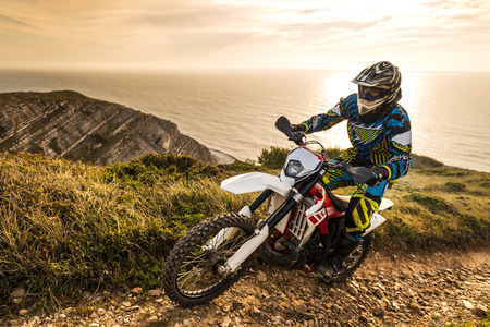 Enduro rider climbing a steep slope against a beautiful sunset on a seascape Standard-Bild