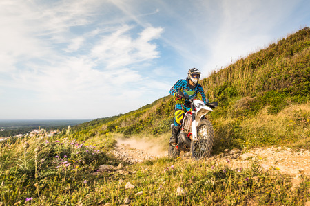 Enduro rider climbing a steep slope against a sunset sky. photo