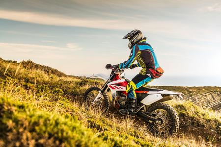 Enduro rider climbing a steep slope against a sunset sky. Standard-Bild