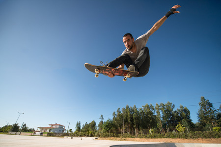 Skateboarder flying over a ramp on blue clear sky. Stock Photo