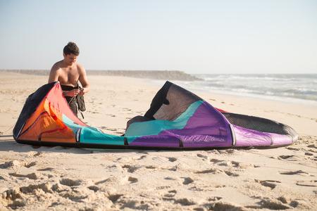 kiter: Kitesurfer prepating his equipment on a beautiful sunset at the beach.