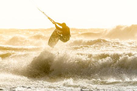 papalote: Kitesurfer que salta en un fondo hermoso del aerosol durante la puesta de sol.
