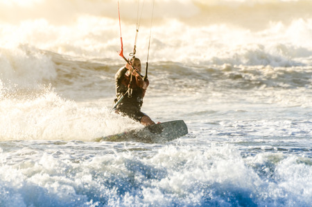 kiter: Kitesurfer in action on a beautiful background of spray during the sunset.