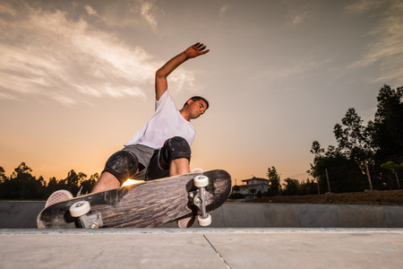 Skateboarder in a concrete pool at skatepark on a beatiful sunset. Banco de Imagens