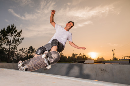 Skateboarder in a concrete pool at skatepark on a beatiful sunset. Фото со стока