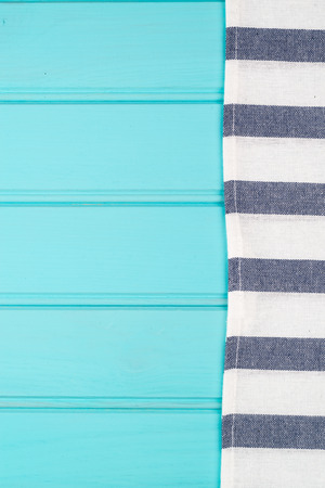 table surface: Blue and white towel over the surface of a wooden table.