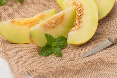 HONEYDEW: Juicy honeydew melon on a wooden table background.